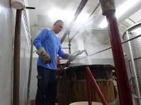 ブドウ液を入れた容器の洗浄作業をするマールーフさん=レバノン東部クサラで2018年11月21日、篠田航一撮影