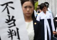 垂れ幕を掲げる弁護士の後ろで肩を落とす大阪朝鮮高級学校の生徒たち=大阪市北区の大阪高裁前で9月27日、小出洋平撮影