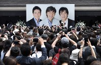 Fans take photos of a picture showing popular singers Hideki Saijo, center, Goro Noguchi, right and Hiromi Go at the entrance of Aoyama Funeral Hall in Minato Ward, Tokyo, on May 26, 2018, after a memorial ceremony for Saijo. (Mainichi/Kimi Takeuchi)