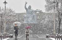 降り続く雪にけむる平和祈念像=長崎市の平和公園で2018年1月11日午後0時3分、徳野仁子撮影