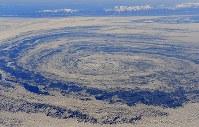 沖で渦巻く流氷。後方左端は知床岬=北海道・オホーツク海で2018年2月2日午後1時56分、本社機「希望」から宮本明登撮影