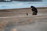 東日本大震災から7年。日の出とともに荒浜地区の海岸を訪れ、花を手向ける男性=仙台市若林区で2018年3月11日午前6時13分、喜屋武真之介撮影