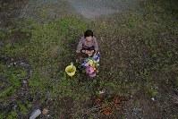 熊本地震から2年。「京子ちゃん今年は来たけんね。長いこと来れんだったけん」本震で亡くなった島崎京子さん宅跡に花などを手向ける友人の女性=熊本県益城町で2018年4月16日午後5時22分、和田大典撮影