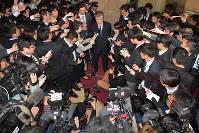大勢の報道陣の前で辞任を表明し、質問に答える財務省の福田淳一事務次官(中央)=東京都千代田区で2018年4月18日午後6時55分、渡部直樹撮影