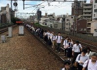 大阪北部地震。止まった電車から線路を使って移動する乗客=大阪市福島区で2018年6月18日午前9時13分、加古信志撮影
