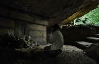 健児の塔の下のガマで手を合わせる男性=沖縄県糸満市で2018年6月23日午前8時28分、津村豊和撮影