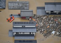 西日本豪雨。小田川が決壊し、洪水になった町で続けられる救助活動=岡山県倉敷市真備町で2018年7月7日午後0時8分、本社ヘリから加古信志撮影