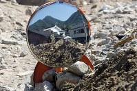 西日本豪雨。土砂に埋もれたカーブミラーにうつる自衛隊員=広島県呉市で2018年7月14日、小川昌宏撮影