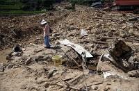 西日本豪雨で消防団の男性が犠牲となった場所に向かって手を合わせた後、手を顔にあてる木坂宮子さん(82)。近所に住み、草取りなども手伝ってくれたという。「まじめな方だったから一生懸命やってくれたんだと思う」と悼んだ=広島県呉市安浦地区で2018年8月6日午後1時48分、小川昌宏撮影