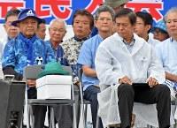県民大会で翁長知事が被るはずだった帽子(前列左)を見つめる謝花喜一郎副知事(同右)=那覇市で2018年8月11日午前11時9分、野田武撮影