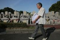 家族や親戚と霊園を訪れ、熊本地震で亡くなった河添由実さんの遺骨を運ぶ父敏明さん。敏明さん一家は地震後ずっと家の仏壇の横に置いていた由実さんの遺骨を、盆が明けたら納骨すると決心した。「近くにいてほしいという気持ちはまだあるばってん、由実も安らかに眠ってもらうごつ」=熊本県益城町で2018年8月19日午前8時4分、和田大典撮影