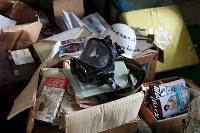 オウム真理教の教団施設から回収され、富士ケ嶺公民館の一室に置かれたままになっているガスマスクやサンスクリット語が書かれた座布団、松本智津夫元死刑囚の写真が表紙の書籍など=山梨県河口湖町で2018年9月6日、小川昌宏撮影