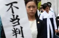 垂れ幕を掲げる弁護士の後ろで肩を落とす大阪朝鮮高級学校の生徒たち=大阪市北区の大阪高裁前で2018年9月27日午後3時6分、小出洋平撮影