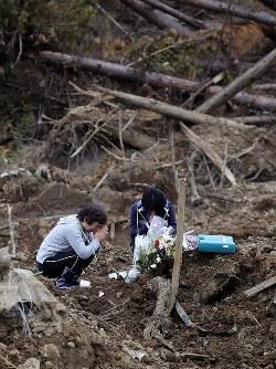 地震発生から1カ月。地震による土砂崩れで3人が亡くなった場所で手を合わせる女性=北海道厚真町で2018年10月6日午後2時38分、貝塚太一撮影