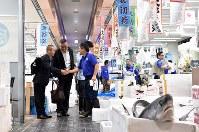開場した豊洲市場の水産仲卸売場で、顧客の男性と笑顔で握手を交わす「山治」の山崎康弘社長(右)=東京都江東区で2018年10月11日午前7時51分、竹内紀臣撮影