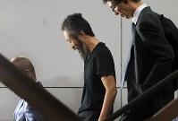 航空機から降り、階段で笑顔を見せる安田純平さん(中央)=成田国際空港で2018年10月25日午後6時36分、梅村直承撮影