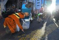ハロウィーンから一夜明け、朝日が昇る中で仮装の姿のままゴミ拾いをする人たち=東京都渋谷区の渋谷センター街入り口で2018年11月1日午前6時51分、手塚耕一郎撮影