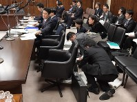 参院法務委員会で外国人労働者の受け入れを拡大する入管法改正案について山下貴司法相(左手前)の答弁の準備をする事務方たち(中央手前)=国会内で2018年12月4日午前11時41分、川田雅浩撮影