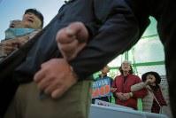 埋め立ての土砂投入が始まった日の翌朝、工事に反対してキャンプ・シュワブのゲート前に立ち、腕を組む人たち=沖縄県名護市で2018年12月15日午前8時26分、和田大典撮影