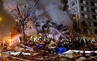 消火活動を続ける消防隊員ら。周辺には建物の残骸が散乱していた=札幌市豊平区で2018年12月16日午後9時24分、貝塚太一撮影