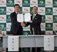 統合に向け、合意書に署名した岐阜大の森脇久隆学長(左)と名古屋大の松尾清一学長=名古屋市中村区で2018年12月25日撮影
