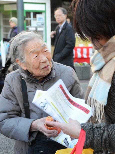 情報提供を呼びかけるチラシを配る宮沢節子さん=東京都世田谷区で2018年12月30日、土江洋範撮影