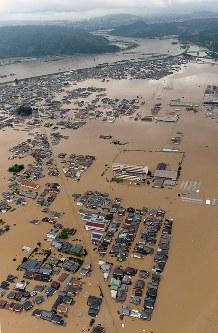 堤防が決壊し、濁流に覆われた倉敷市真備町地区。奥は高梁川=岡山県で7月7日、本社ヘリから加古信志撮影