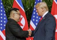 会談冒頭で握手する北朝鮮の金正恩朝鮮労働党委員長(左)とトランプ米大統領=シンガポールで6月12日、AP共同
