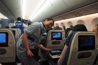 An All Nippon Airways cabin attendant talks to a passenger during a 2019 New Year's sunrise-viewing flight on Jan. 1, 2019. (Mainichi/Kenji Yoneda)
