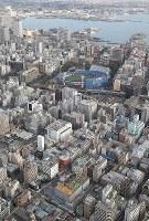 A lodging house where a fire broke out is seen at left bottom from a Mainichi Shimbun helicopter in Yokohama's Naka Ward on Jan. 4, 2019. Yokohama Stadium is seen at center. (Mainichi/Akihiro Ogomori)