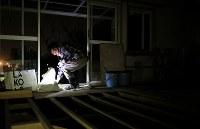 懐中電灯のわずかなで片付けを続ける森末節さんの長女ゆかりさん。掃除道具を手に自宅の中を忙しく動き回っていた=広島県呉市で2018年12月05日、小出洋平撮影