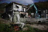 自宅の解体が始まった。重機が少しずつ家の中に入っていく様子を家族から離れ、ひとり見つめる森末節さん=広島県呉市で2018年12月13日、小出洋平撮影