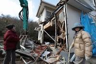 工事が中断すると、家に近寄り、解体の様子を確認する森末直美さん(左)と長女ゆかりさん=広島県呉市で2018年12月13日、小出洋平撮影