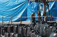 被害が大きかった川沿いはフレコンバッグの応急処置が施され、シートで覆われた建物もある=広島県呉市で2019年1月3日、小出洋平撮影