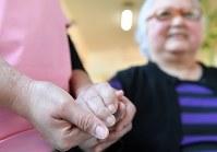 日系ペルー人2世のキシモト・ケイコさん(右)と手をつなぐフィリピン人介護士福祉士候補者=愛知県豊田市で2018年12月15日、大西岳彦撮影