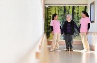 施設の廊下を歩く日系ペルー人2世のキシモト・ケイコさん(中央)とフィリピン人介護士福祉士候補者=愛知県豊田市で2018年12月15日、大西岳彦撮影