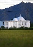 田んぼに囲まれた「岐阜モスク」。奥の山頂には夕日に照らされた岐阜城が見える=岐阜市で2018年9月28日、久保玲撮影