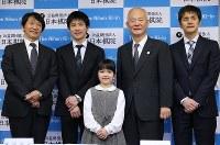 史上最年少のプロ棋士となり、記念撮影する仲邑菫さん(中央)。右は父の仲邑信也九段、右から2人目は日本棋院の団宏明理事長=東京都千代田区で2019年1月5日午後2時34分、小川昌宏撮影