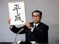 Then Chief Cabinet Secretary Keizo Obuchi holds the new era name of Heisei during a press conference on Jan. 7, 1989 at the prime minister's office in central Tokyo. (Mainichi)