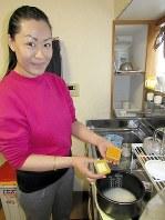 「デシ」を調理中のチョデンさん。手にしているのは、ご飯を炊く前に加えるターメリックだ=東京都豊島区で