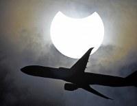 一部が欠けた太陽の前を通過する飛行機=東京都江東区で2019年1月6日午前9時20分、藤井達也撮影