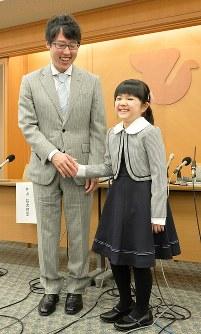 本因坊文裕(左)と握手をして笑顔を見せる仲邑菫さん=東大阪市で2019年1月6日午後4時22分、加古信志撮影