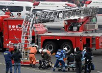 東京消防庁の出初め式の中の消防演技で、新型のはしご車を使って建物の屋上から車いすの人を救助する消防隊員ら=東京都江東区で2019年1月6日午前11時34分、竹内紀臣撮影