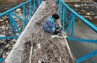 手すりがひしゃげ、流木が残された橋の上で手を合わせる保手浜春美さん=広島県三原市で2019年1月6日午前11時16分、小出洋平撮影