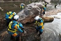 巨石の周りなどで行方不明者の捜索をする警察官=広島県三原市で2019年1月6日午前10時48分、小出洋平撮影