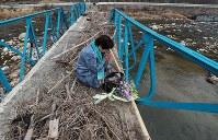 西日本豪雨から半年。手すりがししゃげ、流木が残された橋の上で手を合わせる保手浜春美さん=広島県三原市で2019年1月6日午前11時16分、小出洋平撮影