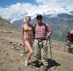 ロシアにある欧州大陸最高峰、エルブルースの中腹でビキニの美少女とツーショット=大村さん提供