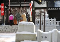 People pay their first visit of the year to Atsuma Shrine in Atsuma, Hokkaido, where a stone lantern (foreground) toppled by the powerful earthquake that struck the town in the northernmost prefecture in September 2018 remains on its side, on Jan. 1, 2019. (Mainichi/Taichi Kaizuka)