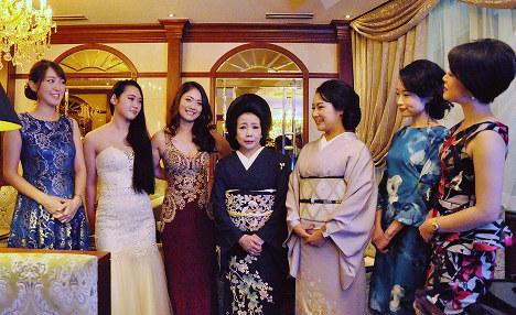 従業員に囲まれる上田利恵さん(中央)=金沢市片町1のクラブ利恵で、岩壁峻撮影