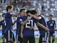 アジア杯【日本・トルクメニスタン】日本の3点目のゴールを決めて、長友と原口から祝福される堂安=UAEのアブダビで2019年1月9日、AP